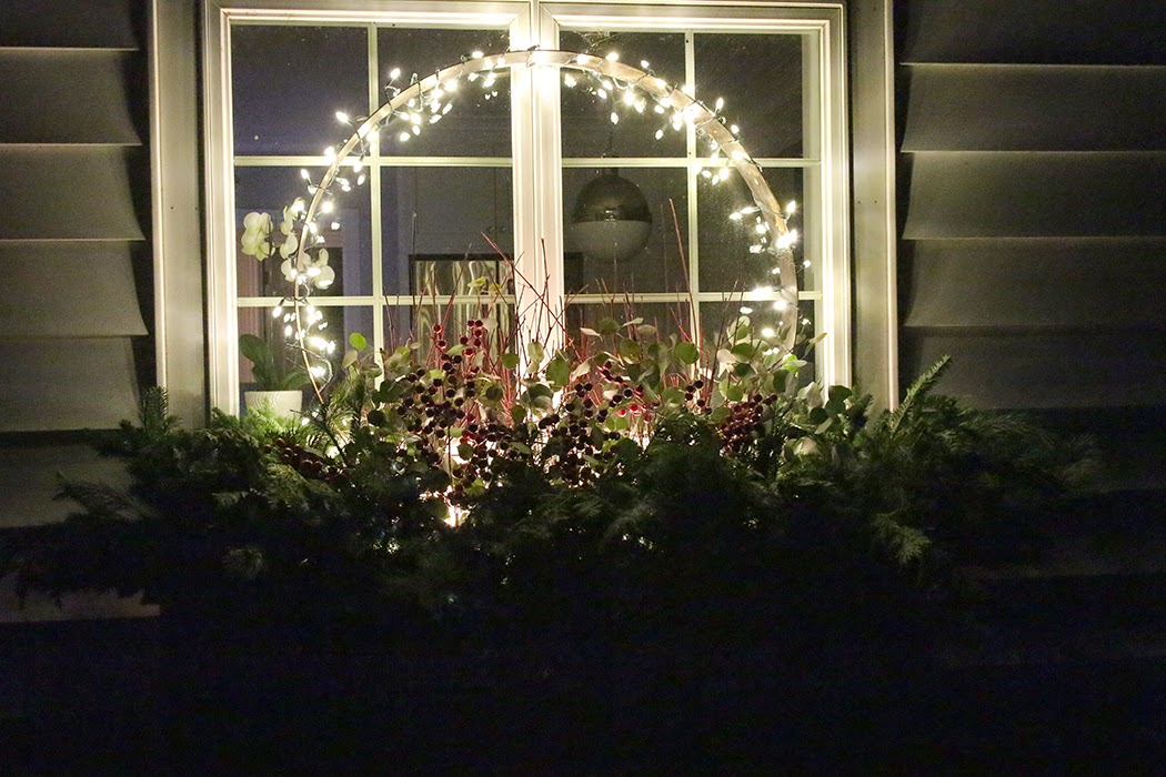 Holiday window box with lighted steel ring at night - The Impatient Gardener