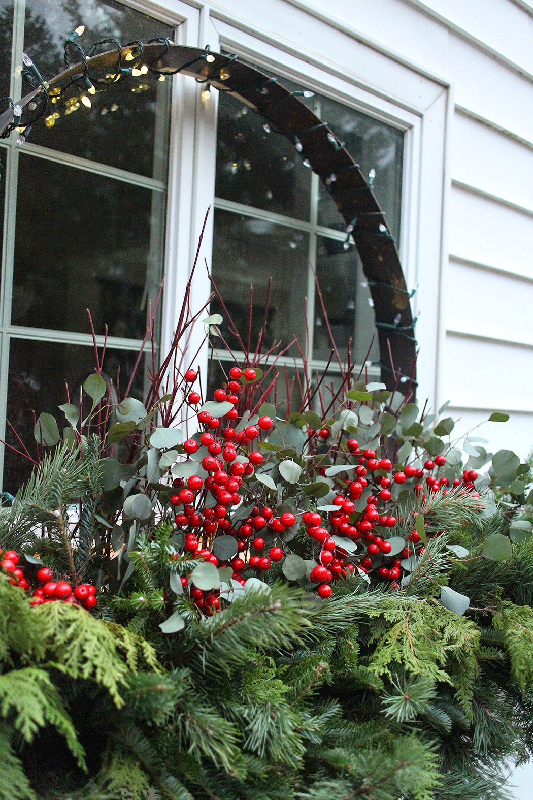 Holiday window box with greens, dogwood twigs, silver dollar eucalyptus, faux berries -- The Impatient Gardener