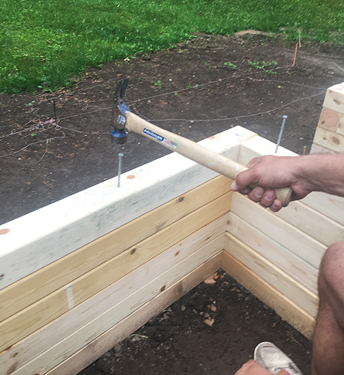 Pounding spikes in a raised bed.