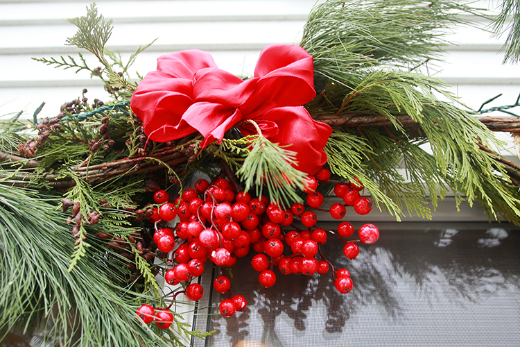 Garland decoration such as a bow and faux berries help brighten up an otherwise plain garland.